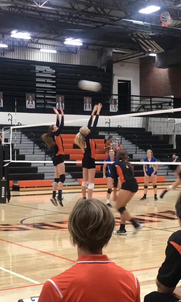 Haley+Carlson+and+Maggie+Masters+jumping+to+block+the+ball