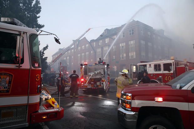Firefighters+pour+water+on+a+fire+at+the+Arthur+Capper+Senior+Building%2C+an+apartment+building+that+houses+senior+citizens.+Four+tenants+are+taken+to+local+hospitals+with+non-life-threatening+injuries.+