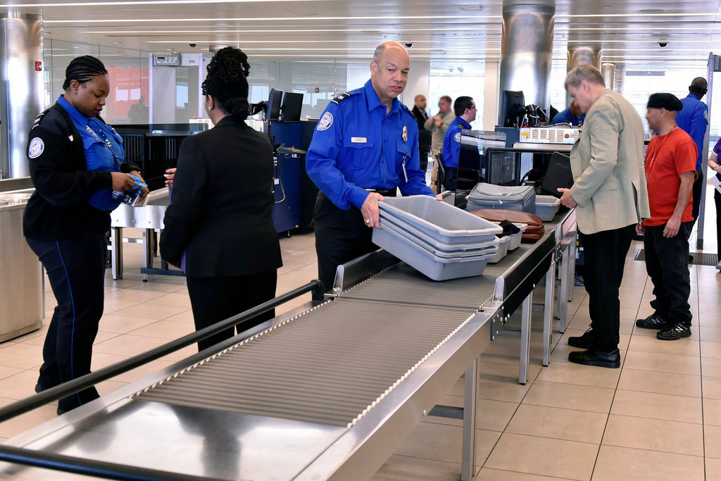 TSA agent insures airport security of passengers. 51,000 TSA agents were affected by the shutdown.