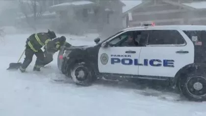 Firefighters help a police officer, whose car was stuck, to get out of the snow. About 1,100 motorists were stranded in Colorado as a ferocious winter storm, called a
