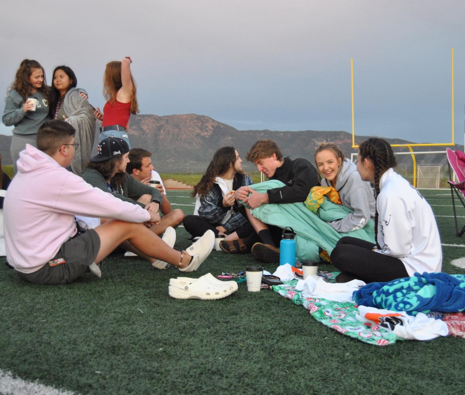 """Students sit together to watch the sunrise on the Don Breese football field on August 24. """"We are rising; the sun is rising,"""" Snouwaert 12 said."""