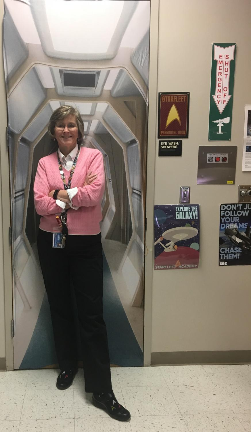 """Mrs. Gregory poses in front of her spaceship themed door cover in her classroom. """"My main interest, just by looking around the room, is Astronomy,"""" said Mrs. Gregory."""