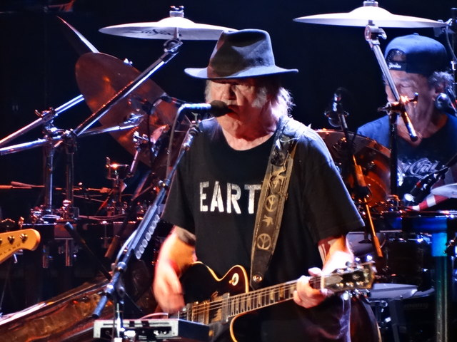 Neil plays at a concert while wearing a pro-environment shirt.