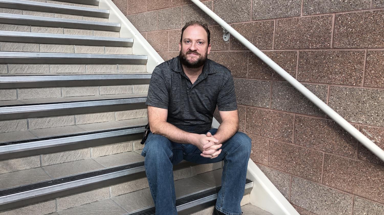 Mr. Moore sits on school stairs.