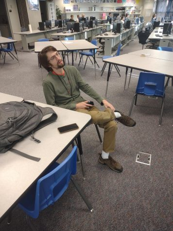 """Seth Wells eSports coach playing on a Xbox that a student brought in. """"I bring in a TV and my switch so kids can play Tetris, stuff like that."""" Wells said."""